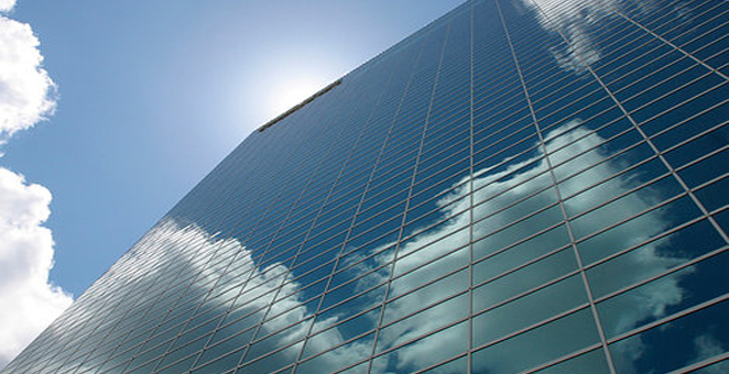 Tall skyscraper viewed from the ground looking up into the bright blue sky. Clouds reflect off the all glass windowed side of the skyscraper.